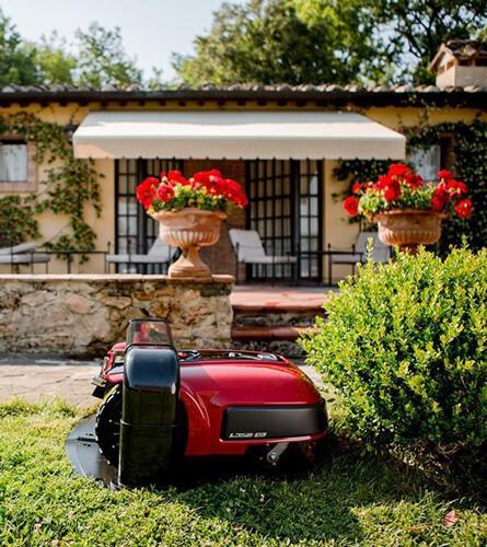 Robot koszący natrawniku przed domem